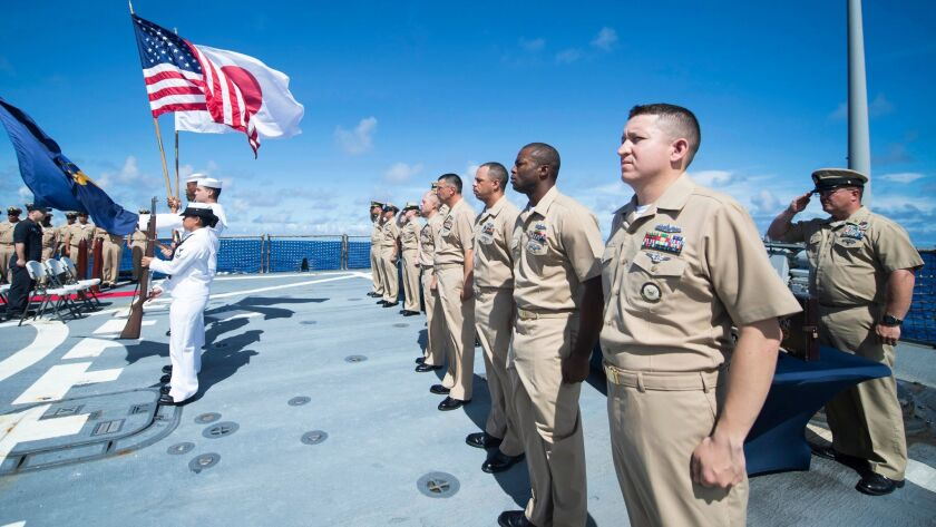 Sailors stand at attention during the national anthem on the flight deck of the Arleigh Burke-class guided-missile destroyer Curtis Wilbur in the Philippine Sea on Sept. 16.