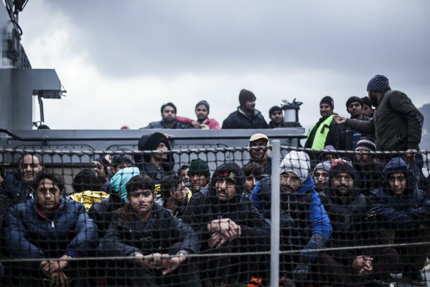 Refugees and migrants arrive on a Greek coastguard patrol boat into the port of Mytilene, of the Greek island of Lesbos, following a rescue operation in a part of the Aegean Sea between Turkey and Greece, on Friday, Feb. 19, 2016. More than 1 million refugees and migrants entered the EU in 2015 fle