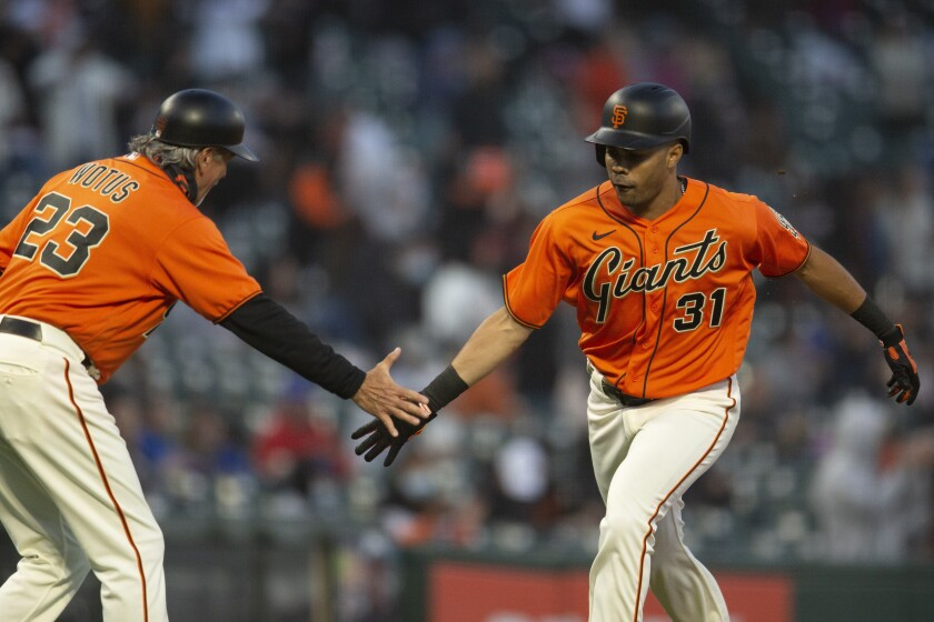 San Francisco Giants' LaMonte Wade Jr. (31) gets a congratulatory handshake from third base coach Ron Wotus (23) after hitting a solo home run against the Chicago Cubs during the fourth inning of a baseball game, Friday, June 4, 2021, in San Francisco. (AP Photo/D. Ross Cameron)