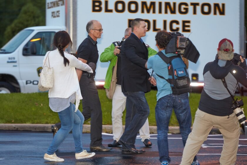 Dentist and trophy hunter Dr. Walter Palmer, left in black short sleeves, walks into his clinic with private security and among members of the media in Bloomington, Minn.