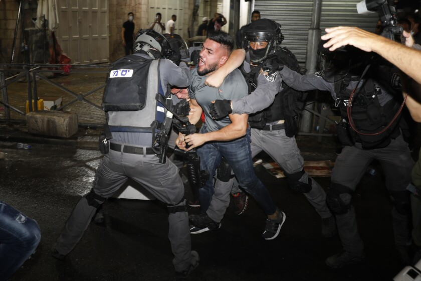 Policías israelíes se enfrentan con manifestantes palestinos cerca de la Puerta de Damasco el domingo 9 de mayo de 2021, a las afueras de la Ciudad Vieja de Jerusalén. (AP Foto/Ariel Schalit)