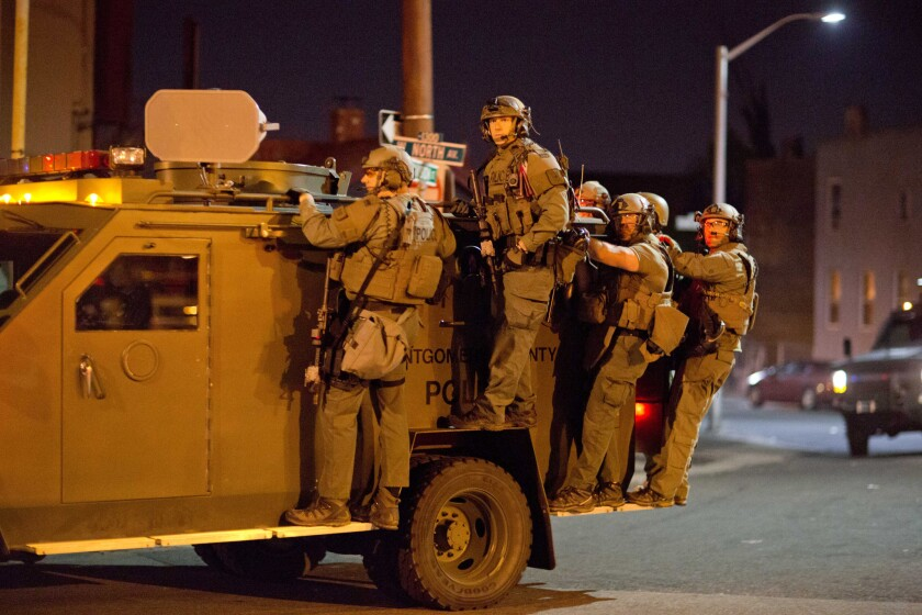Police ride on an armored vehicle through a riot-racked area of Baltimore after a 10 p.m. curfew went into effect.
