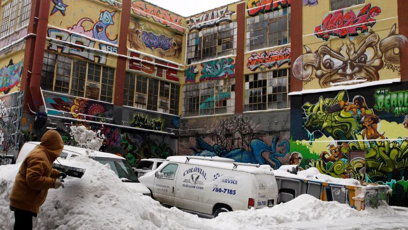 FILE- In this Jan. 26, 2011 file photo, a man shovels snow to clear a driveway near 5pointz graffiti