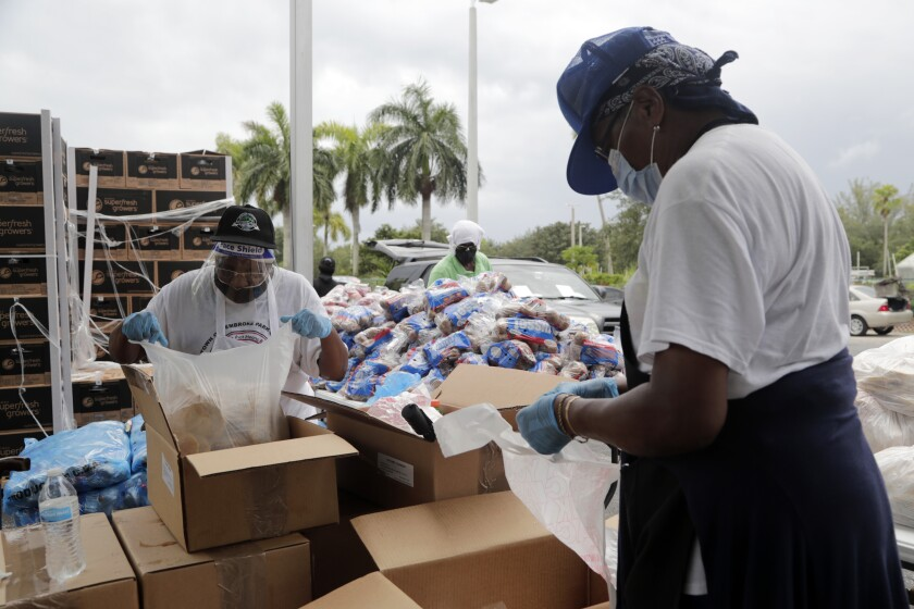 Volunteers load food from cardboard boxes into bags at a food distribution site in Pembroke Park, Florida