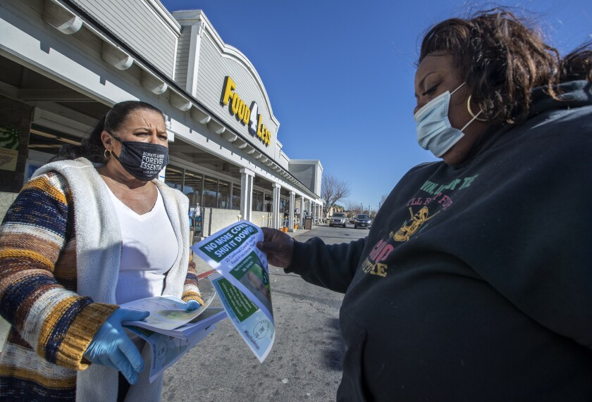 Barbara Hughes, a cashier at Food 4 Less in Palmdale, hands a flier to customer Rona Millage of Palmdale on Friday, notifying her about coronavirus cases at the store.(Mel Melcon / Los Angeles Times)