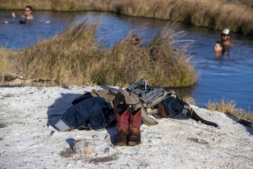Boots and a pile of clothing left on the ground by bathers enjoying  a hot spring in Tecopa, Calif.