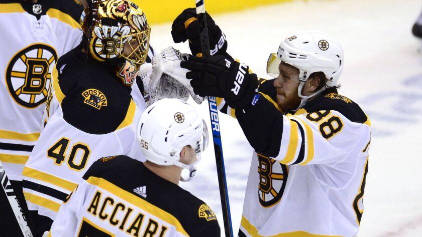 Boston Bruins right wing David Pastrnak (88) celebrates with goaltender Tuukka Rask (40) and center