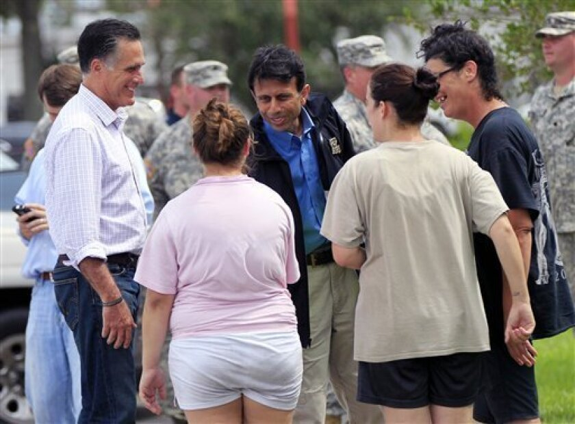 Republican presidential candidate Mitt Romney left, and Louisiana Gov. Bobby Jindal, center, greet residents displaced by Isaac in Lafitte, La., Friday, Aug. 31, 2012. Isaac is now a tropical depression, with the center on track to cross Arkansas on Friday and southern Missouri on Friday night, spreading rain through the regions. (AP Photo/Gerald Herbert)