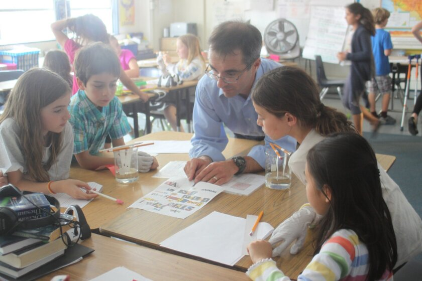 La Jolla Elementary School students Eliana Mahl, Sasha Berger, Innovation Middle School science teacher Tom Nusser, Isabella Millard and Daphnie Tseng work together at a science-based crime study event last June in the school library.