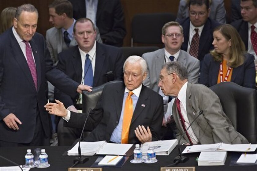 From left, Sen. Chuck Schumer, D-N.Y., standing, Sen. Orrin G. Hatch, R-Utah, and Sen. Chuck Grassley, R-Iowa, confer as the Senate Judiciary Committee meets on immigration reform on Capitol Hill in Washington, Thursday, May 9, 2013. A bill to enact dramatic changes to the nation's immigration system and put some 11 million immigrants here illegally on a path to citizenship is facing its first congressional test as the Senate Judiciary Committee begins considering proposed changes to the 844-pag
