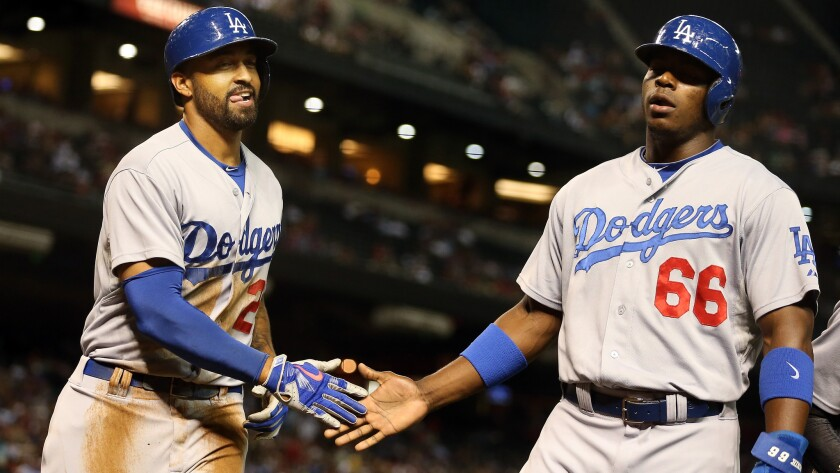 Dodgers outfielder Matt Kemp, left, is congratulated by teammate Yasiel Puig after hitting a run-scoring double against the Arizona Diamondbacks on Aug. 27. Kemp and Puig appeared to get into an argument during Monday's win over the Colorado Rockies.