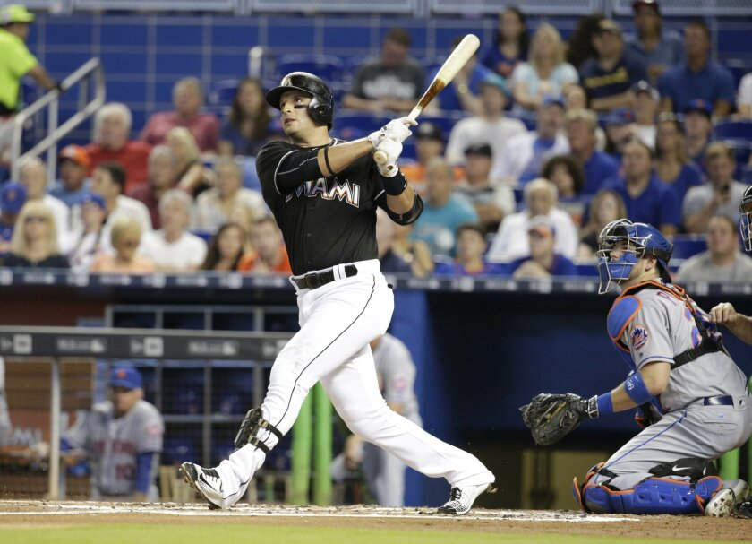 Miami Marlins' Derek Dietrich, left, watches after hitting a solo home run as New York Mets catcher Kevin Plawecki, right, looks on during the first inning of a baseball game, Saturday, June 4, 2016, in Miami. (AP Photo/Lynne Sladky)