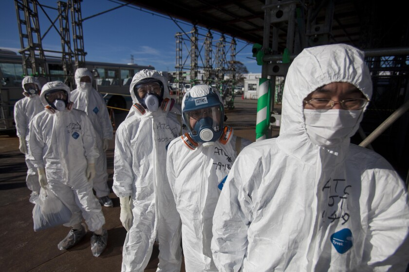 Workers in protective suits and masks wait to enter the emergency operation center at th Fukushima Daiichi nuclear power station in November 2011.