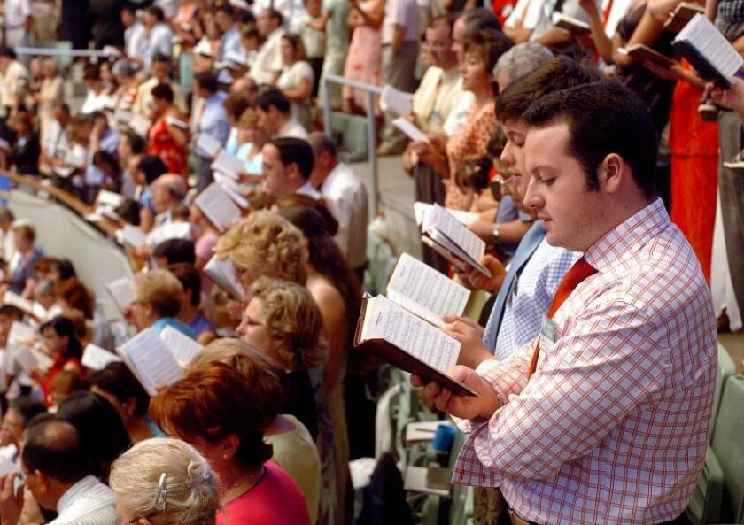 Fieles Testigos de Jehová rezando durando la ceremonia de bautismo celebrada hoy en el Palacio de Vistalegre, en Madrid. EFE/Mondelo/Archivo