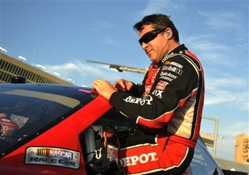 Tony Stewart gets out of his car after taking the pole position during qualifying for Sunday's NASCAR Sprint Cup Series auto race at Atlanta Motor Speedway, Friday, Aug. 31, 2012, in Hampton, Ga. (AP Photo/Rainier Ehrhardt)