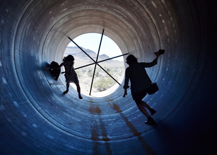 People walk through a Hyperloop tube after the first test of a propulsion s
