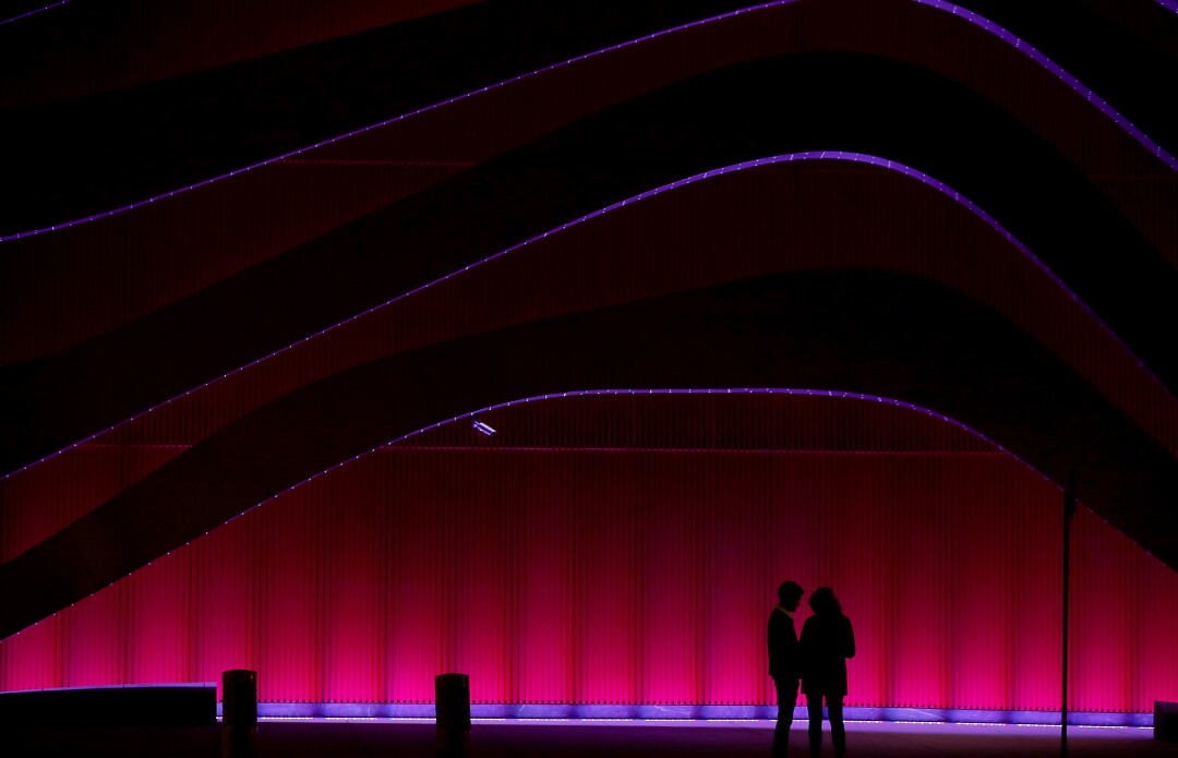 A couple wait for a bus outside the Petersen Automotive Museum in Los Angeles.
