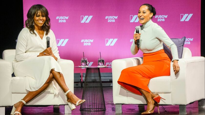 """Former First Lady Michelle Obama and """"black-ish"""" star Tracee Ellis Ross chat during the first day of the two-day United State of Women Summit over the weekend at the Shrine Auditorium in Los Angeles."""