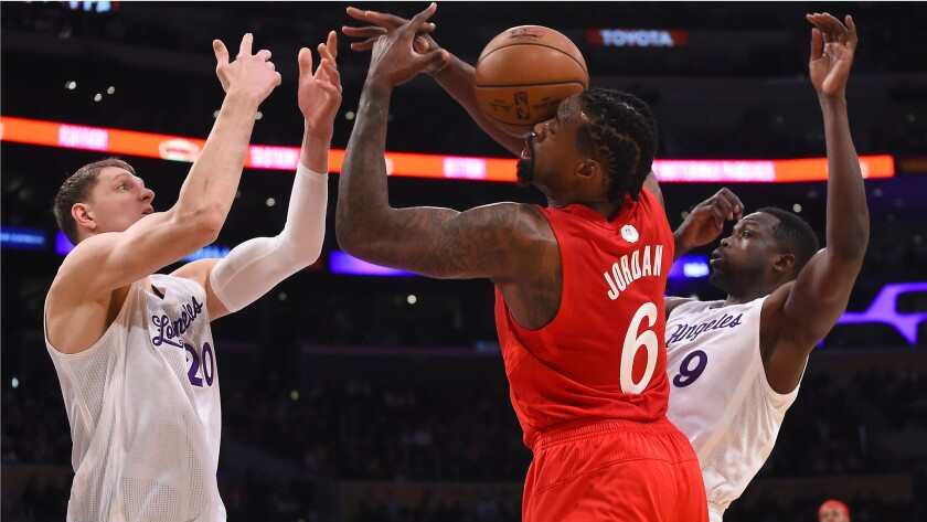 Lakers center Timofey Mozgov (20) and forward Luol Deng battle Clippers center DeAndre Jordan for a rebound during during their Christmas evening game.