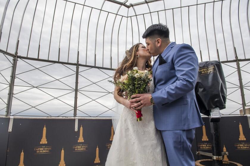 A couple kiss at their wedding