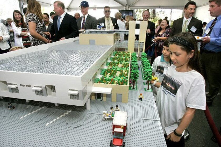 A Lego model of the planned Critical Care Building of Scripps Memorial Encinitas is displayed at an event Thursday, April 8, marking the beginning of expansion. Getting a close look are Olivia Mejia, 8, and her brother (behind her) Nolan, 6. Their mother, Sharon Creal, the hospital's V.P. of financ
