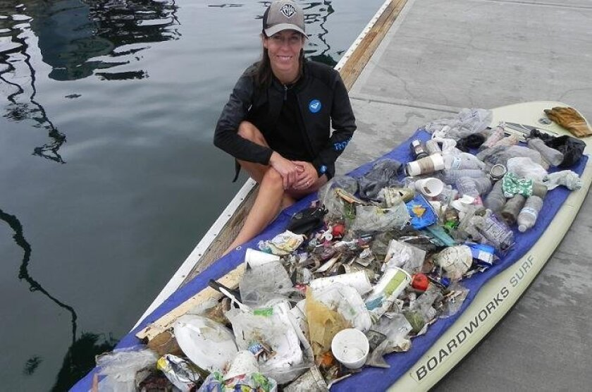 Patti Diaz with her paddle board after a cleanup.
