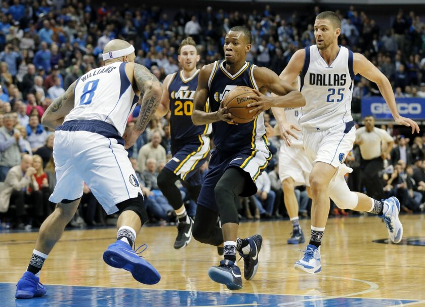 Utah Jazz's Rodney Hood (5) drives to the basket against Dallas Mavericks' Deron Williams (8) for a shot opportunity as Chandler Parsons (25) sprints to help against the play in the second half of an NBA basketball game, Tuesday, Feb. 9, 2016, in Dallas. The Jazz won in overtime 121-119. (AP Photo/