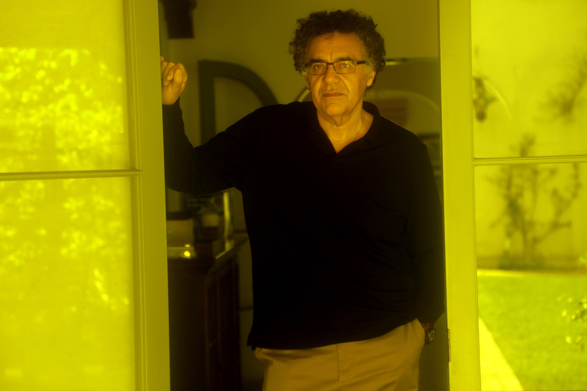 Rodrigo Garcia, looking serious, stands between a set of glass doors that reflect yellow light