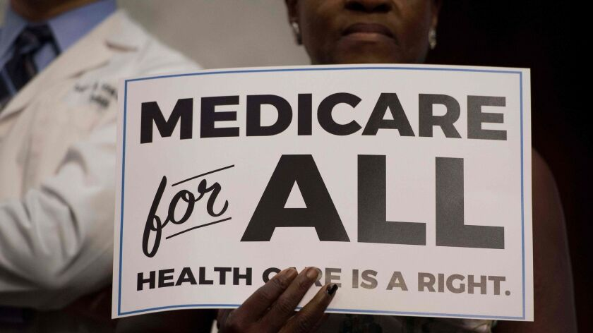 """A member of the audience holds up a placard as Sen. Bernie Sanders (I-Vt.) discusses """"Medicare for all"""" legislation in 2017."""
