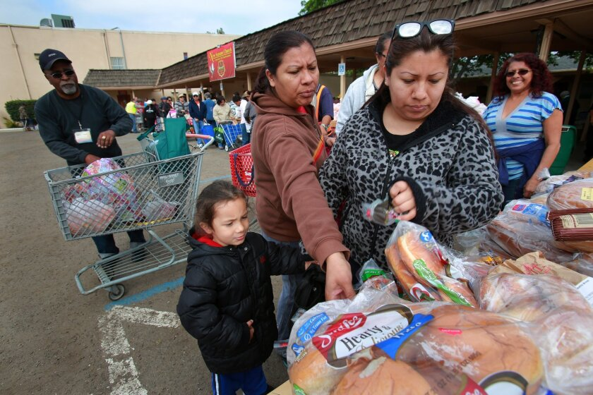 Arian Campbell, 5, waits while his grandmother Hortencia Valle reaches for bread and his mother, Janel Campbell, looks over the  selection at a food distribution event last month at New Seasons Church in Spring Valley. / photo by Peggy Peattie • U-T San Diego