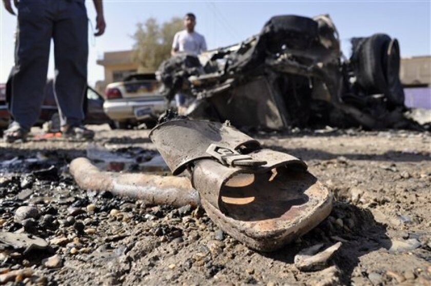 A discarded sandal is seen amid debris and destroyed vehicles the morning after four blasts killed several people in Ramadi, 70 miles (115 kilometers) west of Baghdad, Iraq, Friday, June 3, 2011. The blasts in what was the heartland of the al-Qaida-led insurgency are a reminder of the danger still facing Iraq, as it prepares for the departure of the remaining U.S. troops by the end of this year.(AP Photo)
