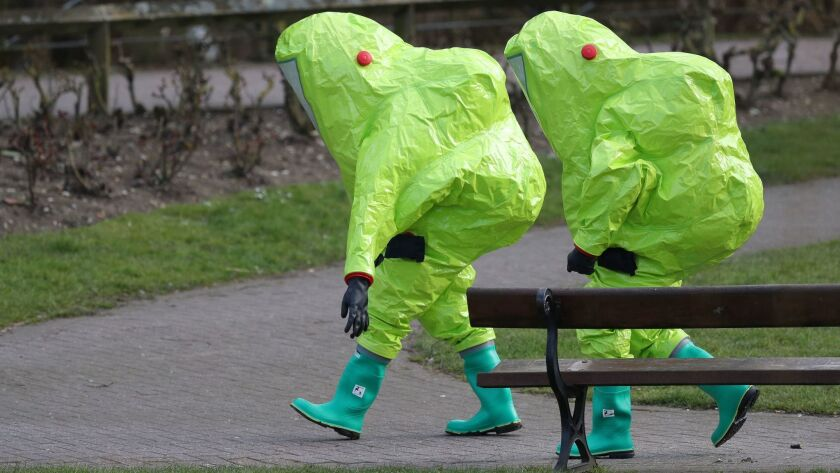 Investigators walk away after securing the covering on a bench in Salisbury, England, where former Russian double agent Sergei Skripal and his 33-year-old daughter, Yulia, were found critically ill by exposure to a nerve agent on Sunday.