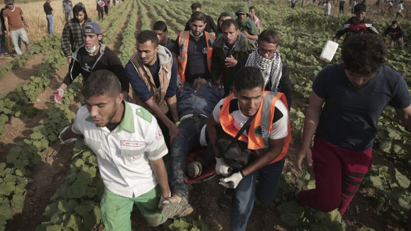 Palestinians medics carry a wounded man during a protest at the Gaza Strip's border with Israel, Fri