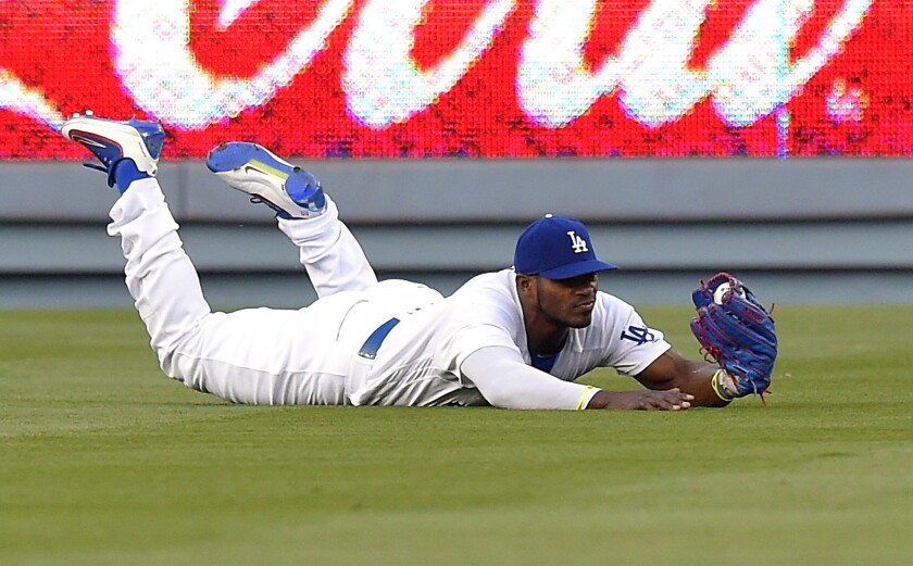 Dodgers outfielder Yasiel Puig slides after making a diving catch on a ball hit by Mets outfielder Juan Lagares during the first inning of a game at Dodger Stadium on May 10.