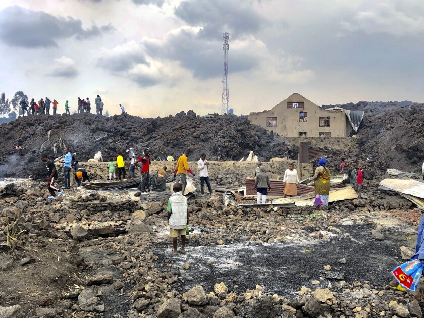 People gather on a stream of cold lava rock following the overnight eruption of Mount Nyiragongo in Goma, Congo, Sunday, May 23, 2021. The volcano unleashed lava that destroyed homes on the outskirts of Goma but the city of nearly 2 million people was mostly spared after the nighttime eruption. Residents of the Buhene area said many homes had caught fire as lava oozed into their neighborhood. (AP Photo/Clarice Butsapu)