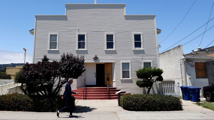 A man walks past the Japanese American Citizens League Hall in Monterey.