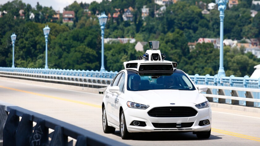 Uber employees test a self-driving Ford Fusion hybrid car in Pittsburgh on Aug. 18.