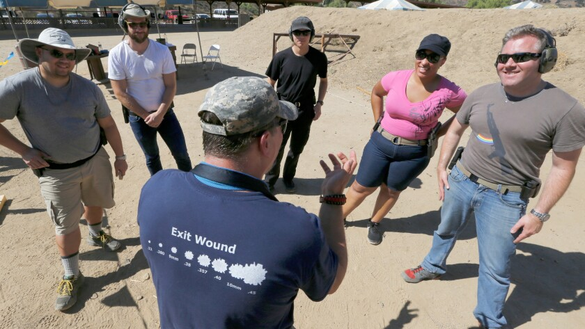 Instructor Jeffrey Bova, center, provides firearms training to a group of gun owners, including West Hollywood Pink Pistols members Elizabeth Southern, second from right, and Jonathan Fischer, right, at a gun range near Piru.