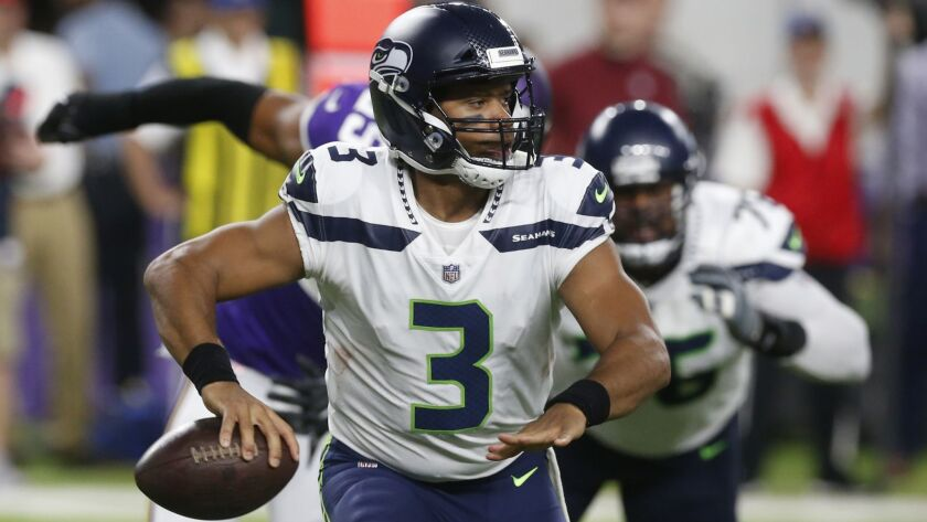 8ef651991 Seattle Seahawks quarterback Russell Wilson looks to throw a pass during  the second half of an NFL preseason football game against the Minnesota  Vikings, ...