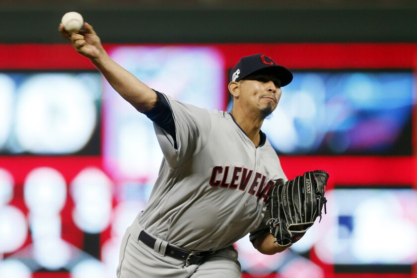 FILE - In this Sept 6, 2019, file photo, Cleveland Indians pitcher Carlos Carrasco throws against the Minnesota Twins in a baseball game in Minneapolis. The Indians' right-hander, who made a dramatic comeback last season after being diagnosed with leukemia, has been cleared to pitch and is thrilled to be back on the field after baseball was shut down during the COVID-19 pandemic. Carrasco said his health is good and his doctors have approved him playing despite the inherent risks. (AP Photo/Jim Mone, File)
