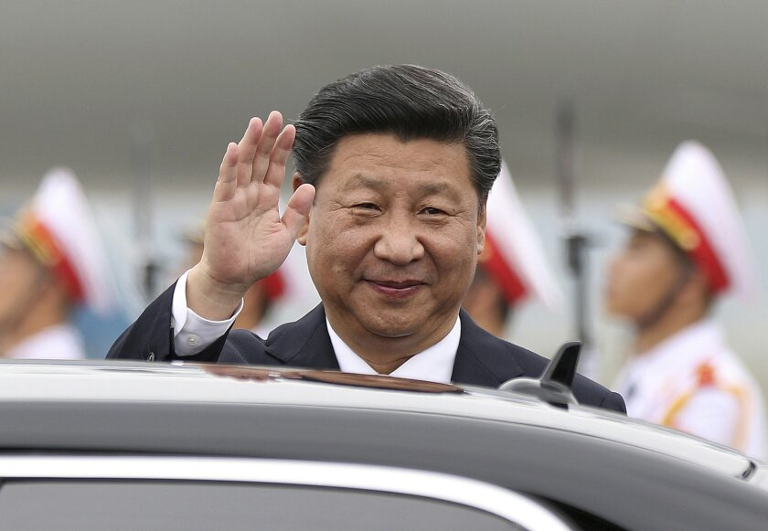 FILE- In this Thursday, Nov. 5, 2015, file photo, China's President Xi Jinping waves as he arrives at Noi Bai International Airport in Hanoi, Vietnam. The leaders of China and Taiwan met Saturday in a historic first since their territories split during the Chinese civil war in 1949.  (Minh Hoang/Po