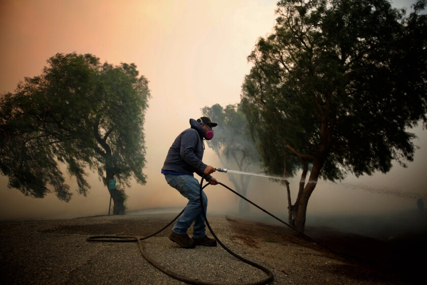 Billy MacFarlane uses a garden hose to douse embers on his family's ranch