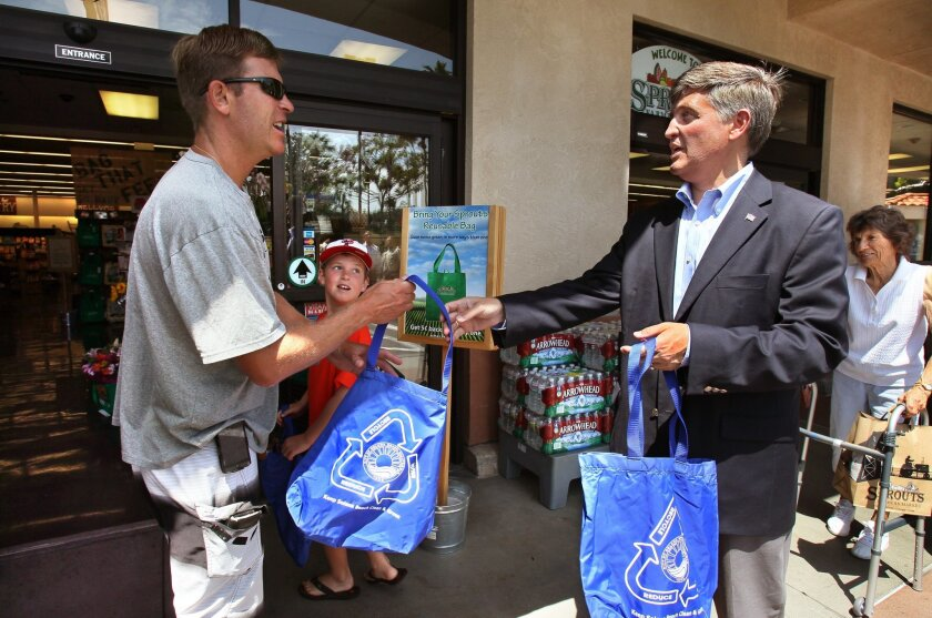 Solana Beach Deputy Mayor Dave Roberts, right, Thursday hands out a reusable shopping bag to customer Steve Haferkamp and his 9-year-old son, Grant, in front of the Sprouts store on Lomas Santa Fe Drive in Solana Beach.