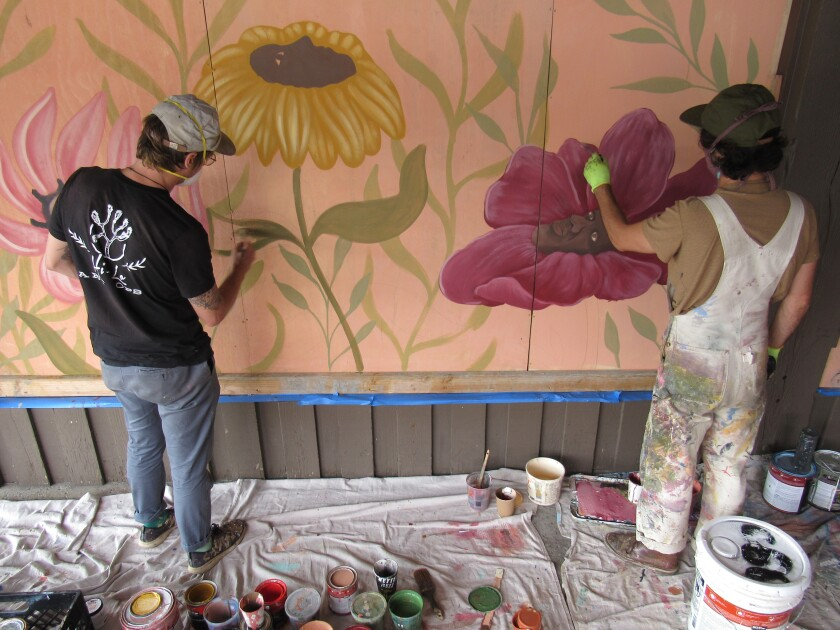 Aaron Glasson (left) and Jonny Alexander work on a mural together in the La Mesa Springs Shopping Center.