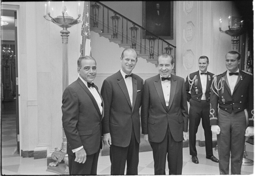 In this Nov. 4, 1969, image provided by The Richard Nixon Library & Museum, President Richard Nixon, center, stands with Prince Philip, second from left, prior to a black tie state dinner. (The Richard Nixon Library & Museum via AP)