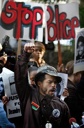 Shango Abiola shouts and raises his fist during a press conference in front of the Criminal Courts building in Los Angeles over the hearing going on inside for former Bay Area Rapid Transit officer Johannes Mehserle, who is charged with the shooting death of 22-year-old Oscar Grant last year.