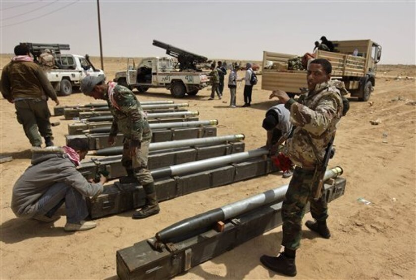 Libyan rebel fighters prepare rockets for use at a position west of Ajdabiya, Libya, Wednesday, April 6, 2011. NATO rejected criticism from Libyan rebels over the pace of its military campaign in Libya, saying Wednesday that its airstrikes against Moammar Gadhafi's forces are increasing every day. (AP Photo/Ben Curtis)