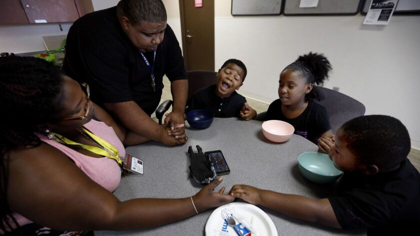 A family prays before they eat dinner at the Union Rescue Mission in Los Angeles on July 19.