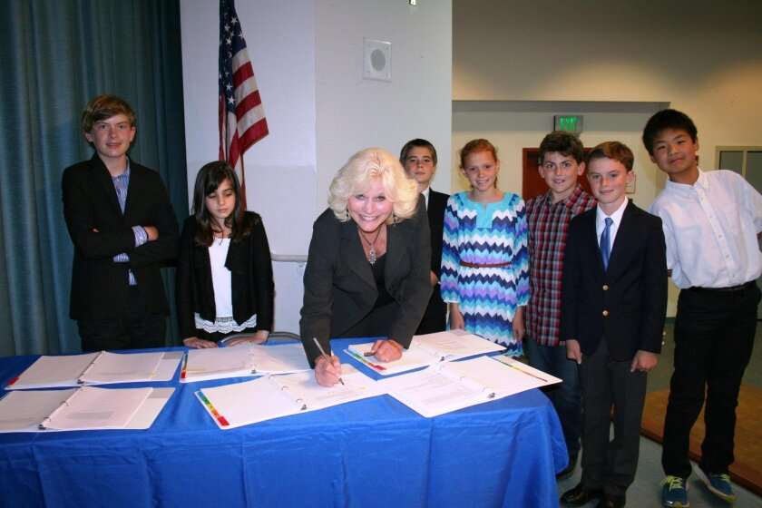 Encinitas School Board President Emily Andrade signs to accept the students' Storm Water Pollution Prevention Plan.