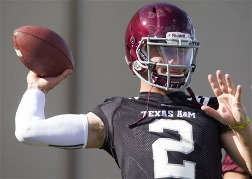 Texas A&M quarterback and Heisman Trophy winner Johnny Manziel throws during football practice, Monday, Aug. 5, 2013, in College Station, Texas. The NCAA has started an investigation as to whether Manziel received payment for signing hundreds of autographs on photos and sports memorabilia in January. (AP Photo/Patric Schneider)
